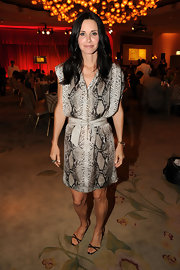 Courteney Cox teamed her snakeskin print shirtdress with a pair of delicate black sandals.