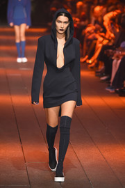 Bella Hadid showed some cleavage in a hooded LBD with a plunging neckline while walking the DKNY runway.