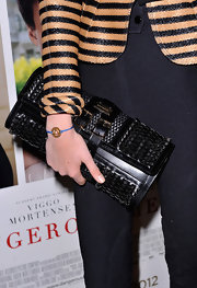 Cara Delevingne styled her look with a buckled woven leather purse while out at the UK premiere of 'A Dangerous Method.'