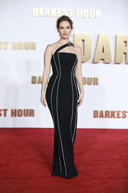 Lily James cut a shapely silhouette in a body-con black one-shoulder gown by Burberry at the UK premiere of 'Darkest Hour.'