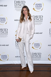 Gisele Bundchen rocked an all-white pantsuit and tie-neck blouse combo at the David Lynch luncheon.