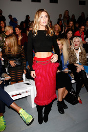 Abbey Clancy styled her top with a flirty red tweed skirt.