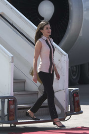 Queen Letizia of Spain touched down in Haiti wearing a sleeveless pink button-down and black trousers by Hugo Boss.