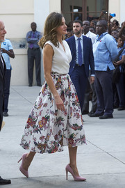 Queen Letizia of Spain was breezy and chic in a sleeveless white wrap top while touring Haiti.