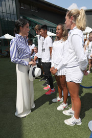 Meghan Markle paired white wide-leg pants with a striped shirt, both by Ralph Lauren, for day 12 of Wimbledon 2018.