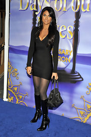 Nadia wears a tiny black bandage dress that shows off her slim figure and accentuates her bright blue eyes.