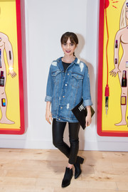 Lily Collins kept the edgy vibe going with a pair of black leather skinnies.