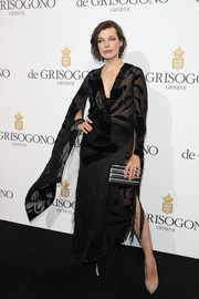 Milla Jovovich donned a sheer black dress with drapey sleeves and a fringed skirt for the De Grisogono party.