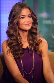 Denise Richards looked fresh and glam at the FOX Studios in a purple dress paired with layered gold necklaces. She finished off the look with long curls.