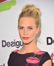Poppy Delevingne brightened up her look with a bold orange lip.