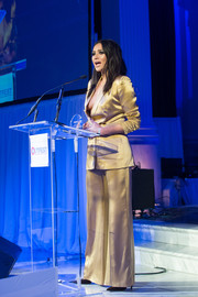 Shay Mitchell displayed her cleavage in a plunging gold Kayat pantsuit while speaking on stage at the Outfest UCLA Legacy Awards dinner.