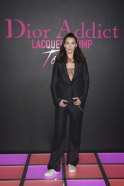 Bella hadid donned a black suit, which she sexed up with a sheer bandeau top, for the Dior Addict Lacquer Plump party.