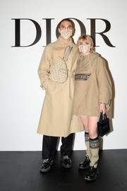 Maisie Williams arrived for the Dior Spring 2021 show carrying a black logo purse from the label.