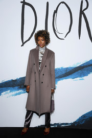 Naomi Campbell teamed a gray wool coat with a graphic turtleneck and satin pants for the Dior Homme Fall 2019 show.