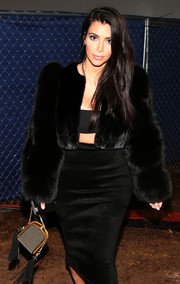 Kim Kardashian paired an Alexander McQueen metallic purse with a Tom Ford fur coat for an ultra-luxe look during the DirecTV Super Saturday Night.