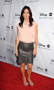 Showing her support for television Courtney wears bowed flats that match well with her gray leather skirt.