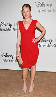 Julie went bold in a bright red, v-neck cocktail dress with nude accessories and a low ponytail.