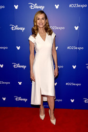 Holly Hunter went modern in an ivory midi dress with slashed shoulders and an asymmetrical hem that she paired with a cuff bracelet by  Alexis Bittar during Disney's D23 Expo 2017.