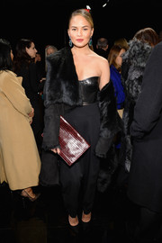 Chrissy Teigen was edgy-glam at the DKNY 30th anniversary fashion show in a black fur coat layered over a leather bustier.