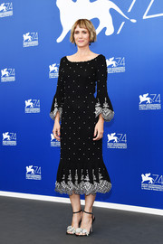 Kristen Wiig completed her monochrome ensemble with a pair of intricately embellished sandals by Sophia Webster.