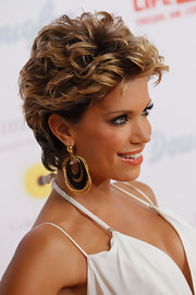 Sylvie van der Vaart accessorized with her signature big earrings, here in a gold dangle hoop style.