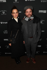 Jenny Slate matched a black chain-strap bag with her coat and boots for the 'Sunlit Night' celebration.