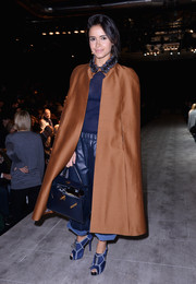 A bronze cape added major drama to Miroslava Duma's casual outfit when she attended the Dsquared2 fashion show.