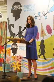 Kate Middleton visited Roe Green Junior School wearing a demure blue maternity dress by Seraphine.