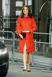 Kate Middleton paired her stylish coat with a black suede clutch by Emmy.