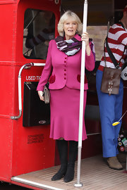Camilla wears a bright pink skirt suit out in London and pairs the look with a multi-colored scarf and black boots.