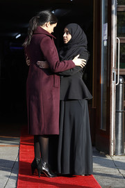 Meghan Markle teamed black Givenchy booties with a plum wool coat for her visit to Hubb Community Kitchen.