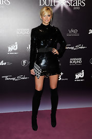Lena went for a daring look in knee-high black boots with a sparkling mini.