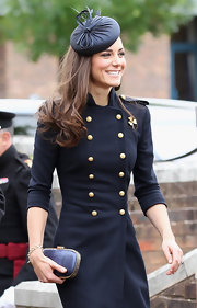 Kate Middleton kept her navy ensemble demure with a matching hard case clutch with gold trim.
