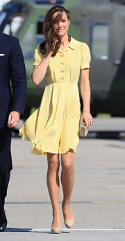 Kate Middleton looked simple yet elegant in a silky lemon dress and nude platform pumps.