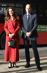 Kate Middleton paired a black leather purse with a red coat for the launch of the 'Hold Still' community exhibition.