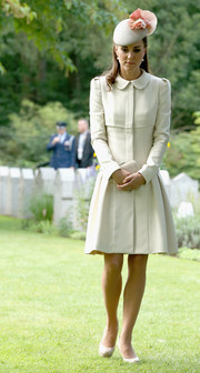 Kate Middleton looked appropriately prim and proper in a cream-colored Alexander McQueen coat dress while touring a World War I cemetery.