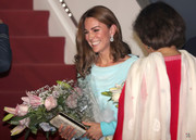Kate Middleton paired a gold clutch by Zeen with a draped blue dress for her arrival in Pakistan.