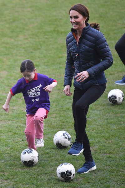 Kate Middleton kept warm in a navy puffer jacket by Barbour while playing football at the Windsor Park Stadium in Belfast.