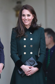 Kate Middleton paired a textured black leather clutch with a green coat dress for day one of her Paris trip.