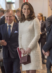 Kate Middleton showed off her impeccable maternity style with this long-sleeve white tweed dress by Alexander McQueen while touring Sweden.