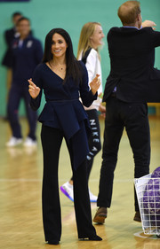 Meghan Markle teamed her blouse with black Altuzarra slacks.