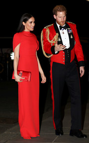 Meghan Markle matched her gown with a buckle-embellished red satin clutch by Manolo Blahnik.