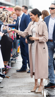Meghan Markle cut a stylish figure, as always, in a classic nude Burberry trenchcoat while meeting fans in Auckland, New Zealand.