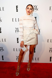 Olivia Culpo attended the E! + Elle + IMG party wearing a white Isabel Marant Etoile blouse with a ruffle collar and sheer lace stripes.