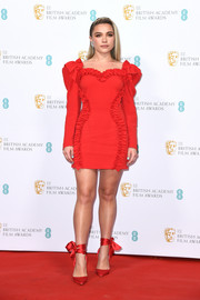Florence Pugh matched her frock with a pair of red ankle-wrap pumps by Christian Louboutin.