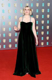 Greta Gerwig went for an elegant dark green velvet gown with bejeweled shoulder straps at the 2020 EE British Academy Film Awards.