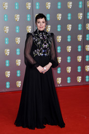 Olivia Colman looked regal in a black Alexander McQueen gown with a floral-embroidered bodice and sheer sleeves at the 2020 EE British Academy Film Awards.