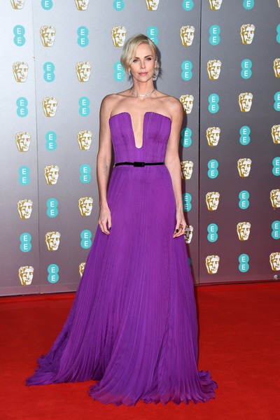 Charlize Theron looked phenomenal in a strapless magenta gown by Dior Couture at the 2020 EE British Academy Film Awards.