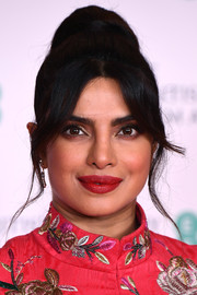 Priyanka Chopra-Jonas styled her hair into a high ponytail with wavy tendrils for the 2021 BAFTAs.