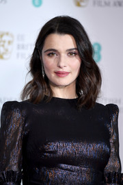 Rachel Weisz wore her hair in shoulder-length waves with an off-center part at the EE British Academy Film Awards.